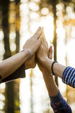 Closeup of four female hands joined together high up in the air Royalty Free Stock Photo