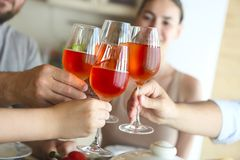Closeup of four glasses with rose wine being clinked together stock photo