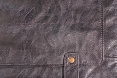 Closeup fragment of Natural brown leather with rivet and stitches.  Stock Images