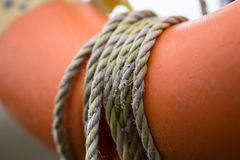 Closeup of frayed rope wrapped around an orange lifebuoy by a river. stock photography