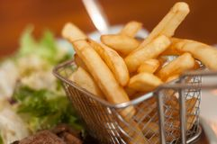 French fries in little metallic basket in a plate at. Closeup of french fries in little metallic basket in a plate at restaurant Stock Images