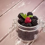 Red raspberries and blackberries in a glass jar with a leaf of mint, 1x1 size stock photography