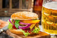 Closeup of fresh burger and a cold beer Stock Photos
