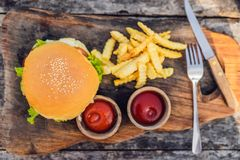 Closeup of fresh burger with French fries on wooden table with bowls of tomato sauce. lifestyle food stock image