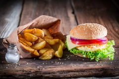Closeup of fresh burger with fried egg and fries. On old wooden table stock image