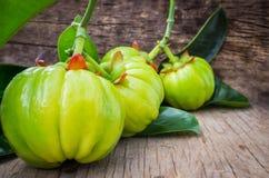 Closeup of fresh garcinia atroviridis fresh fruit on wooden back Stock Photo