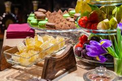 Closeup of fresh honeycombs cut into cubes in transparent square glass bowl at buffet, cinnamon sticks, fruits, macaroons, stock photos