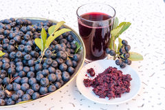 Closeup of fresh juice and jam of ripe black chokeberry Aronia melanocarpa in glass and berry in pot on white textured backgroun royalty free stock photography