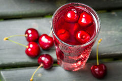 Closeup of fresh juice with sweet cherries and ice. On old table Stock Images