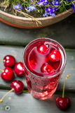 Closeup of fresh juice with sweet cherries and ice Stock Photo