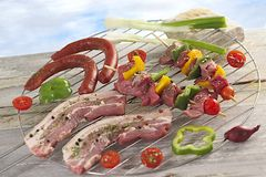 Closeup of fresh meat and sausages on barbecue grid Stock Images