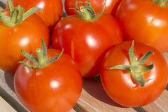 Closeup of fresh organic tomatoes. On a teak table Stock Photo