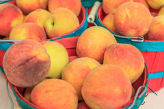 Closeup of Fresh Peaches in Baskets royalty free stock photos