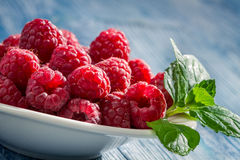 Closeup of fresh raspberries with green leaf. On old wooden table Stock Photo