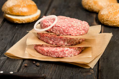 Closeup fresh raw ground beef meat cutlets with onion ring. On a wooden table Stock Images