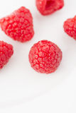 Closeup of fresh red raspberries on a white plate. Macro shot of ripe fresh raspberries lying on a plate in high angle view Stock Photo