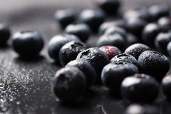 Closeup of fresh ripe blueberries on a black stone background with copy space. Selective focus Royalty Free Stock Photos