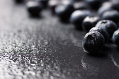 Closeup of fresh ripe blueberries on a black stone background with copy space. Selective focus Royalty Free Stock Photography