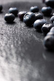 Closeup of fresh ripe blueberries on a black stone background with copy space. Vertical, selective focus Royalty Free Stock Photos