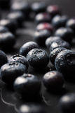 Closeup of fresh ripe blueberries on a black stone background with copy space. Vertical, selective focus Stock Photo