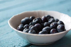 Closeup of fresh ripe blueberries in a bowl on a blue wooden background. Selective focus Stock Photos