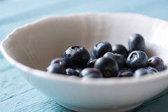 Closeup of fresh ripe blueberries in a bowl on a blue wooden background. Selective focus Royalty Free Stock Images