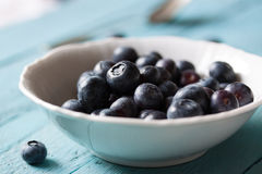 Closeup of fresh ripe blueberries in a bowl on a blue wooden background. Selective focus Royalty Free Stock Photo