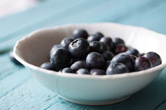Closeup of fresh ripe blueberries in a bowl on a blue wooden background. Selective focus Stock Image