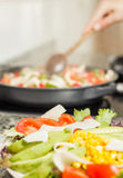 Closeup of fresh salad dish and female cooking in a pan Royalty Free Stock Images