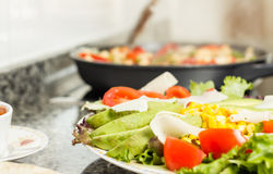 Closeup of fresh salad dish and female cooking in a pan Stock Image