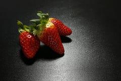 Closeup of fresh strawberries on black background Royalty Free Stock Image