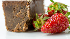 Closeup of fresh strawberries next to a chocolate cake Royalty Free Stock Images