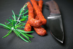 Closeup of fresh thin sausages on black stone background Royalty Free Stock Photos