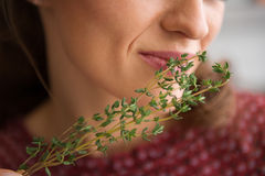 Closeup of fresh thyme being smelled by an elegant woman Stock Photo