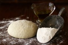 Homemade pizza dough. Closeup of freshly homemade pizza dough on wooden board with olive oil and flour Royalty Free Stock Image