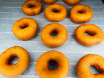 Closeup of freshly made dark brown doughnuts. On baking paper Stock Image