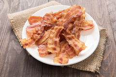 Closeup of fried bacon strips on white plate Stock Images