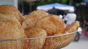 Closeup Fried buns with sesame seeds in a basket on the market stock video