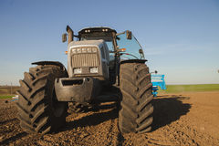 closeup front view tractor on big wheels on ploughed field Royalty Free Stock Photo