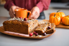 Closeup of fruit and seed loaf with womans hands holding mug Royalty Free Stock Photos