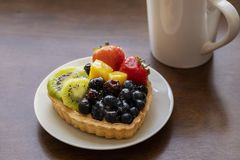 Closeup of fruit tart dessert  with strawberries, kiwi, cheese cream and hot black coffee. In a white cup on a wooden table. Copy space stock photo