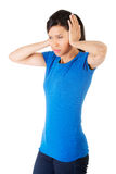 Closeup of frustrated young woman holding her ears Royalty Free Stock Photos