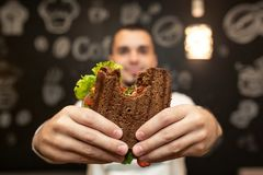 Closeup funny blurred protrait of young man hold bitten sandwich by his two hands. Sandwich in focus. dark background stock photos