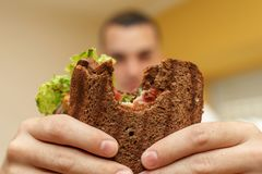 Closeup funny blurred protrait of young man hold bitten sandwich by his two hands. Sandwich in focus. light background royalty free stock image