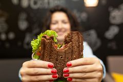 Closeup funny blurred protrait of young woman hold bitten sandwich by her two hands. Sandwich in focus. dark background royalty free stock photos
