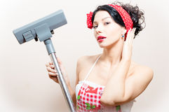 Closeup on funny charming young beautiful brunette woman pin-up girl with vacuum cleaner raised up hand straightens hair. Closeup portrait on funny charming Stock Photo