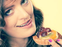 Closeup funny woman eating fruit cake Stock Photography
