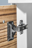 Closeup of furniture cabinet modern clip hinge with amortization Royalty Free Stock Photo