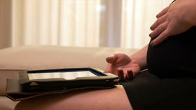 Closeup of future mom browsing the tablet PC app and touching her pregnant tummy stock footage