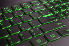 Closeup of gamer laptop keyboard green illumination, backlit keyboard, english letters.  royalty free stock images